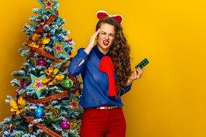 stressed woman near Christmas tree w