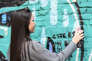 Woman drawing graffiti with spray pa