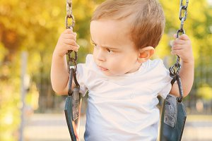 Baby having fun on a swing in a park