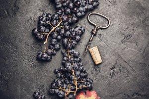 Fresh grape, cork and corkscrew on d