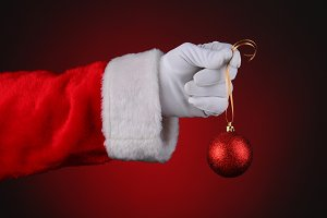 Santa Hand Holding Red Ornament