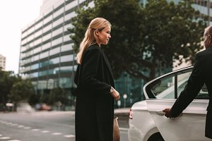 Young businesswoman taking taxi