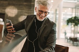 Smiling businessman in earphones