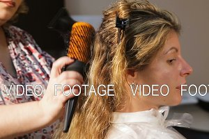Hairdresser woman dries the hair