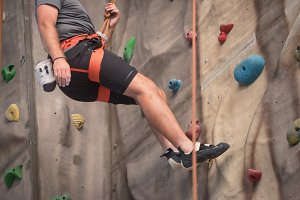Young man practicing rock climbing o