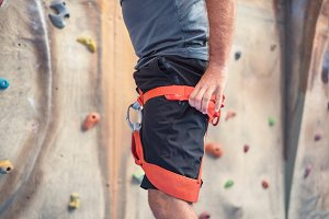 Rock wall climber wearing safety har