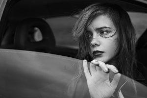 Sad girl in the window of the car
