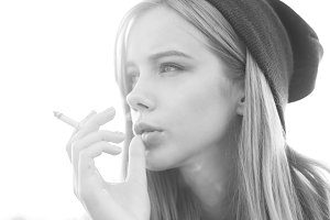 beautiful girl in a hat smokes