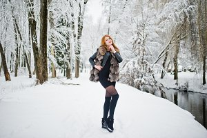 Red haired girl in fur coat walking