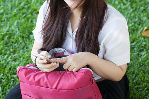 Female student is playing phone