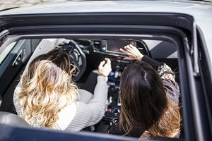 two women singing in the car