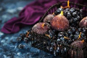 Fresh figs and purple grape in baske