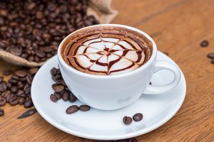 Hot coffee and coffee beans on woode