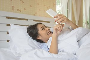 Happy woman using smart phone on bed