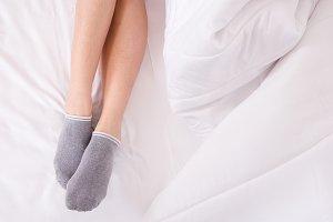 Legs of women on white bed