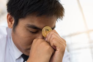 Stress businessman holding bitcoin.b