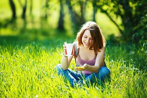 Girl sitting on a meadow with coffee