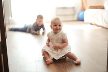 Toddler girl sits floor with brother by  in People