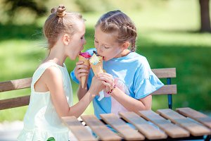 Little girls eating ice-cream outdoo
