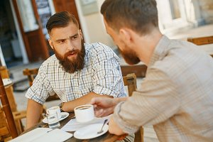 two men drink coffee at a cafe