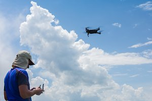 man and his drone, quadrocopter in a