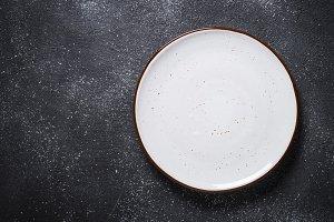 Empty white plate on dark stone