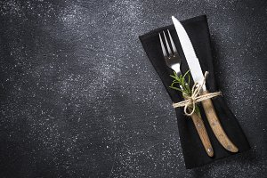 Cutlery and napkin on stone table
