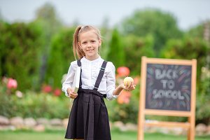 Happy little schoolgirl with a chalk