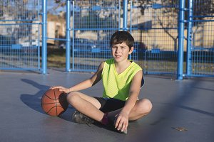Young basketball player sitting on t
