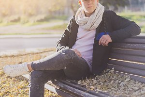 Stylish teenager sitting on a wooden