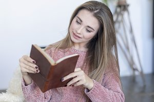 Relaxed woman reading a book on a so