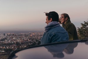Smiling couple on a hilltop looking