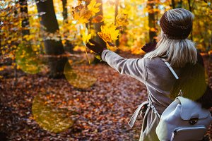 Woman throwing autumn leaves into