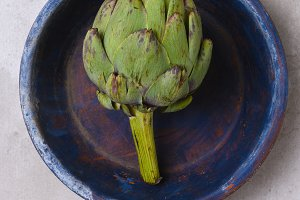 Artichoke on a blue plate on light g
