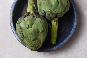 Two artichokes in a blue bowl on a m