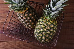 Two Pineapples in a metal shopping b