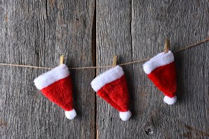 Three Santa hats hanging from a piec