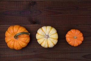 Three decorative pumpkins on a rusti