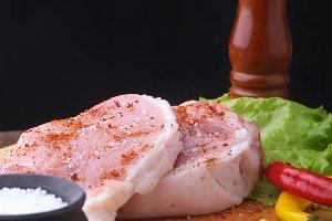Raw steak, chop on a rustic cutting