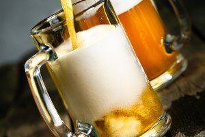 Pouring beer in glasses on rustic