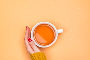 Woman holding cup with hot tea