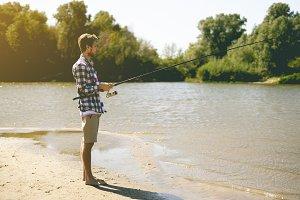young bearded man fishing standing o