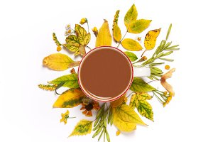 up of coffee in yellow leaves on a w