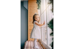 little girl is standing by window on