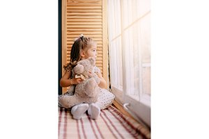 little girl is sitting near window
