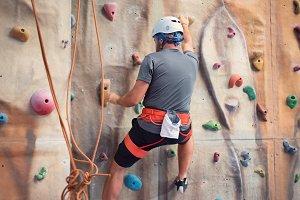 Young man practicing rock climbing