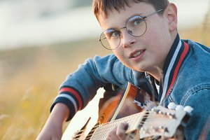 Young teen boy playing on acoustic