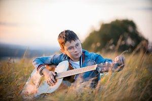 Young teen boy tuning a guitar