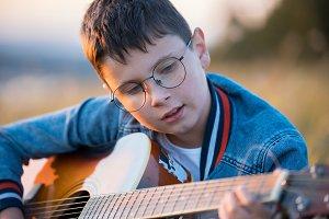 boy guitarist sitting in the field