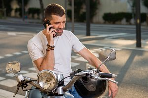 Man with scooter speaks by phone